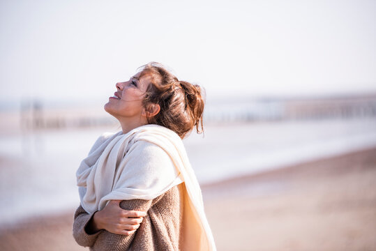Smiling woman with arms crossed looking up at beach on sunny day