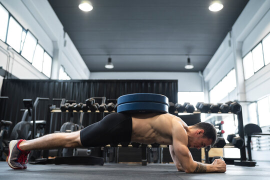 Male athlete doing plank position in health club