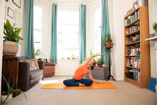 Mature woman doing arm raised stretching exercise at home