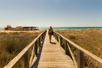 Woman walking along beachside boardwalk Fotobehang
