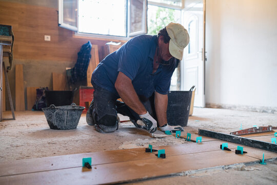 Mature man laying cement on parquet floor in house