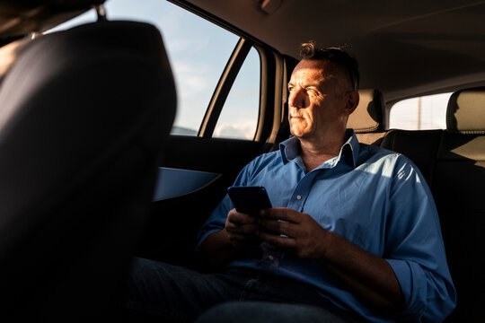 Mature male professional looking away while sitting with smart phone in car