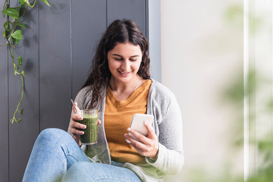 Young woman with smoothie using mobile phone while sitting at home