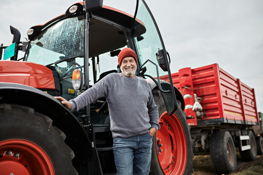 Smiling mature farmer standing with hand in pocket against red tractor at farm