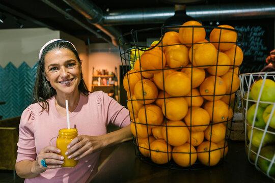 Smiling mature woman holding fresh juice in mason jar while standing by oranges in metallic basket at cafe