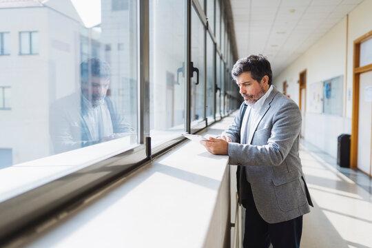 Professor using digital tablet standing by window sill in corridor at university