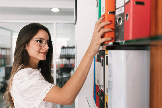 Businesswoman taking file from shelf while standing at office