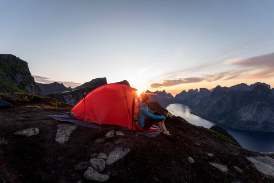 Woman sitting in camp on mountain during sunset at Reinebringen. Lofoten, Norway