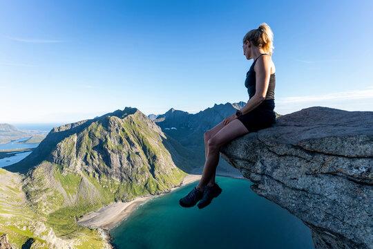 Woman looking at view while sitting on mountain at Ryten, Lofoten, Norway
