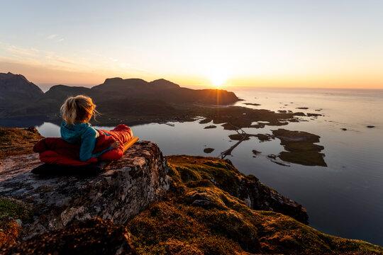 Hiker admiring sunset view while lying in sleeping bag at Volandstinden, Lofoten