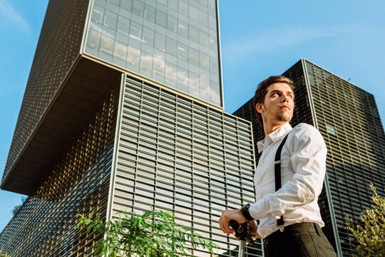 Businessman in city, office buildings in background