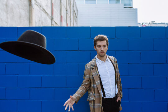 Stylish man wearing checked jacket throwing black hat against blue wall