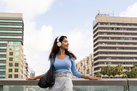 Beautiful young businesswoman listening music through headphones while leaning on railing