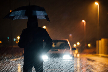 Young man with umbrella standing in front of car dutimng a rainy night Fotomurales