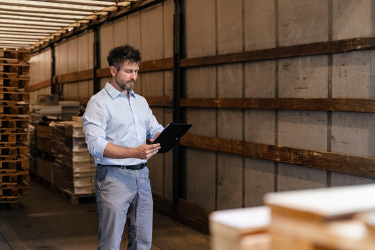 Male inspector with digital tablet loading material while standing in delivery truck