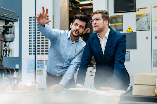 Manager doing hand gesture while discussing with businessman at manufacturing industry