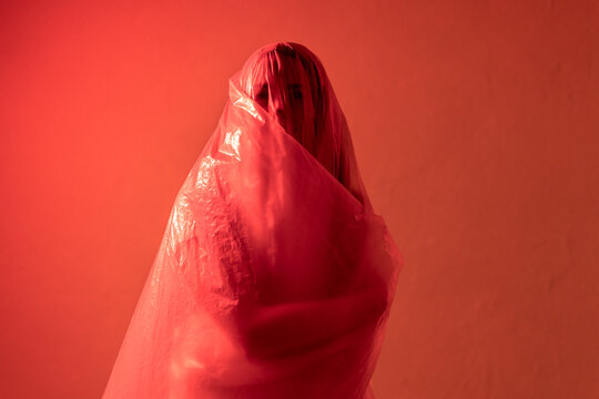 Young woman hugging herself while covered in plastic standing against wall during pandemic
