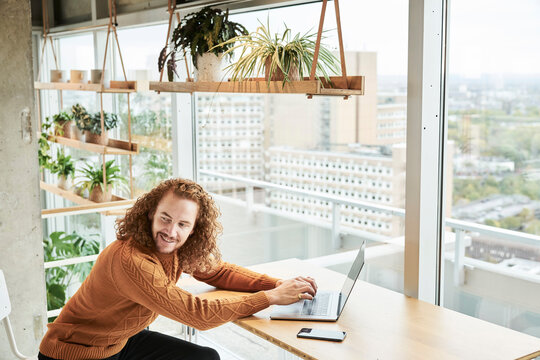 Redhead man looking over shoulder while using laptop sitting at home