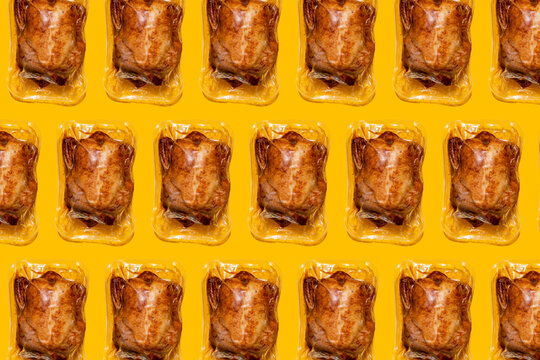 Roasted chicken in airtight packaging on yellow background