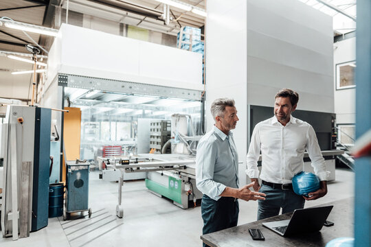 Male engineers discussing over laptop in manufacturing industry