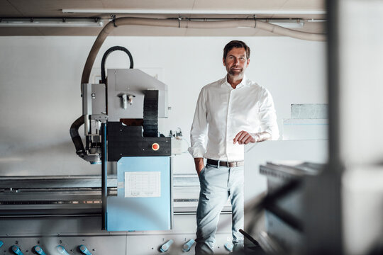 Confident manager with hand in pocket standing by manufacturing equipment in industry