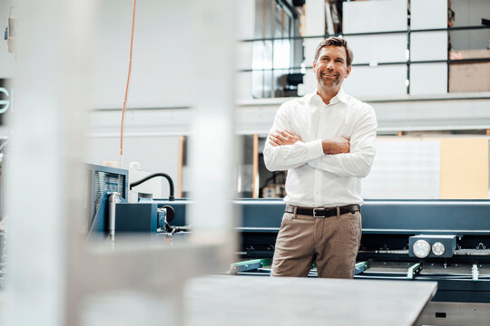 Smiling male engineer with arms crossed standing against manufacturing equipment in industry