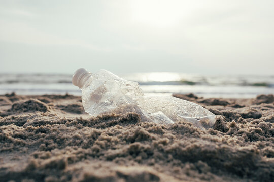 Plastic water bottle on sand at beach