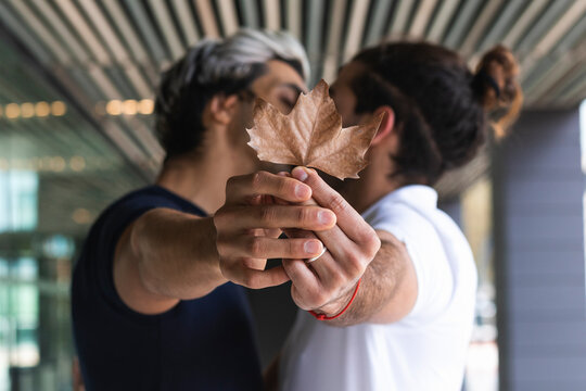 Homosexual couple showing maple leaf while kissing in city