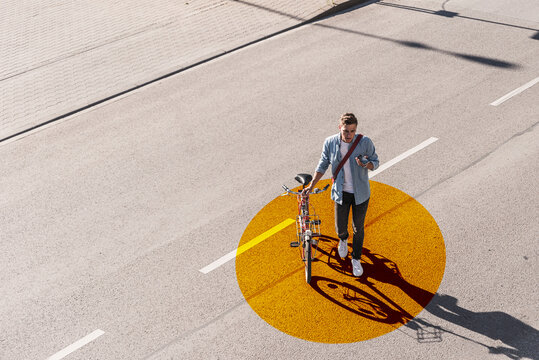 Man with wheeling bicycle using mobile phone while walking on road with gold colored circle