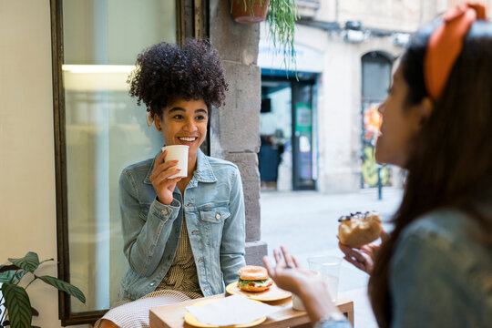 Female friends talking while having food and drink sitting by window at cafe