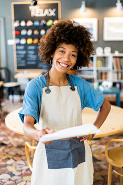 Happy female owner holding menu while standing with hand on hip at coffee shop
