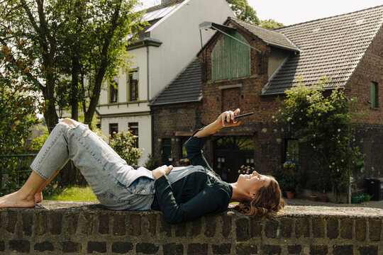 Young woman lying on a brick wall at a farmhouse using smartphone