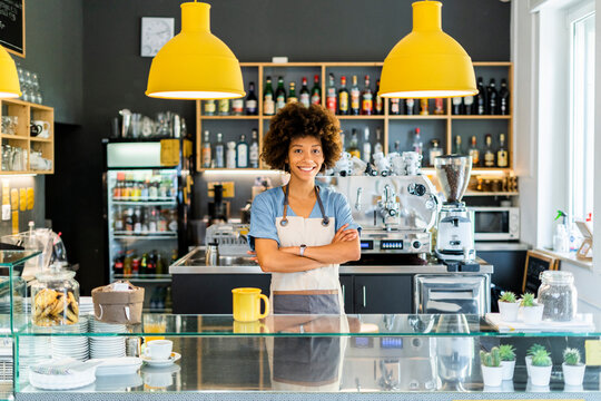 Happy female barista standing arms crossed in cafe