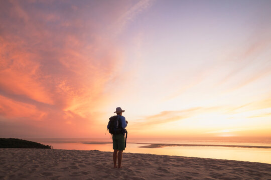 Senior man with backpack looking at Atlantic ocean against sky during sunset, Nouvelle-Aquitaine, France