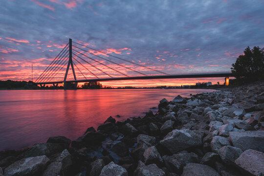 Germany, North Rhine-Westphalia, Wesel, Rocky bank of Rhine at dramatic sunset with Niederrheinbrucke Wesel bridge in background