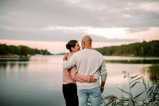 Rear view of smiling couple with arm around standing against lake during sunset