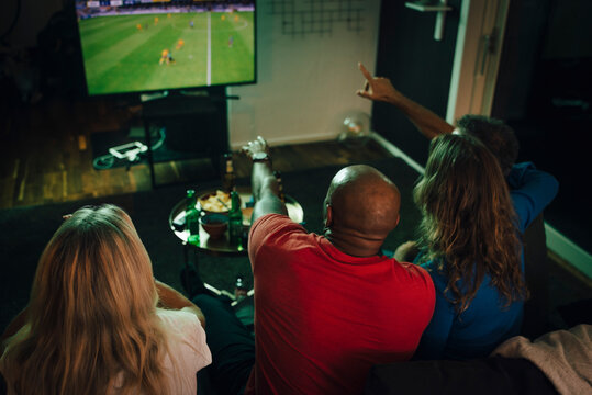 High angle view of friends watching sports on TV while sitting on sofa in living room