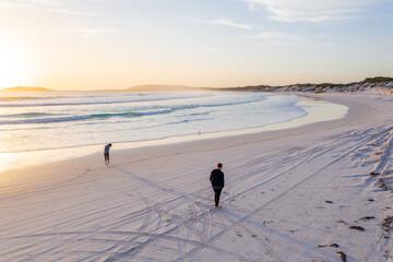 Couple walking along Wharton beach at sunset.  Fotobehang
