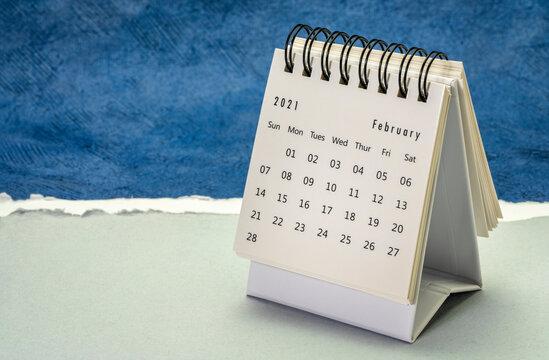February  2021- small spiral desktop calendar against handmade paper, season,  time and business concept