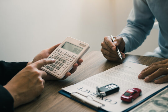 Finance manager of the car showroom is calculating the cost of reserving a new car for the customer while signing a car purchase contract.