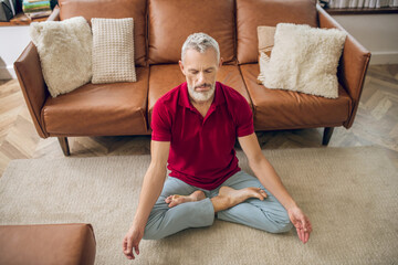 Grey-haired man sitting on the floor in a lotus pose