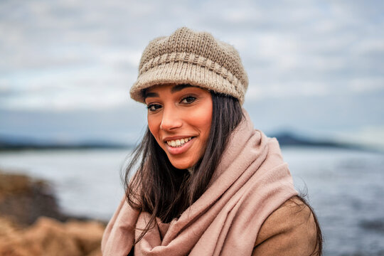 Cute Hispanic young woman with long black hair looking at camera posing outdoor in sea resort with big pink scarf, beige wool hat, and toothy smile - Beautiful female model head and shoulders portrait