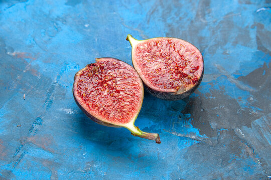 Above view of split fresh black mission figs on blue background