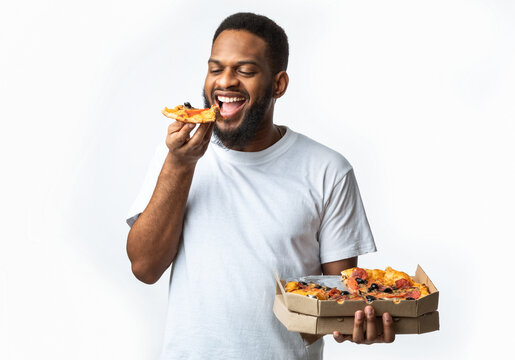 Hungry Black Guy Eating Pizza Holding Box Standing In Studio