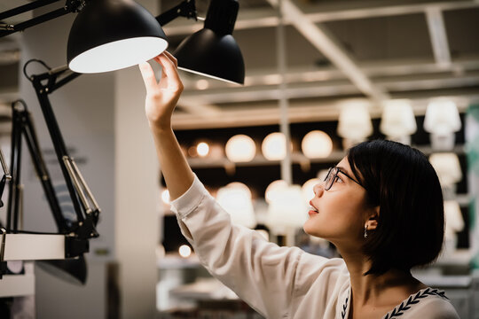 Asian young short hair beautiful woman wearing glasses choosing new lamp to buy at furnishings lighting store