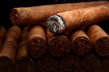 Tobacco cuban havana cigars romeo and julia burned with ash. Beautiful macro background in low key.