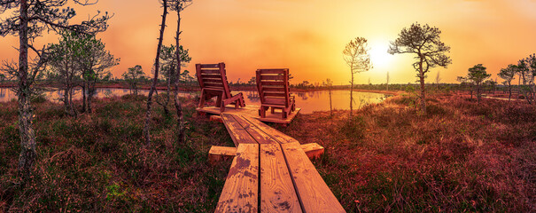 Sunset over the Great Kemeri bog in the Kemeri National Park near Jurmala, Latvia. Empty wooden chairs where you can relax and enjoy view of sunset over pond and swamp.