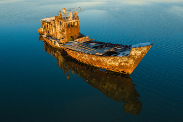 aerial view to old rustic ship wreck in water in summer day in sunset