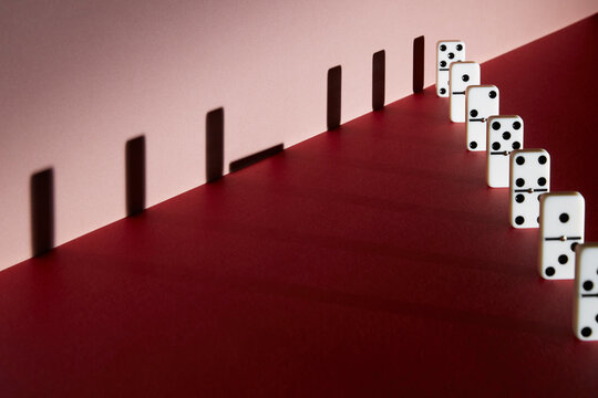 Dominoes and shadow social distancing on red background