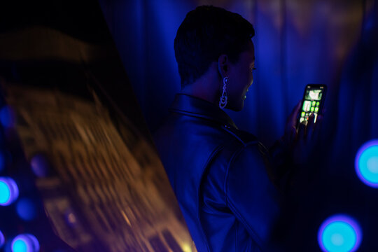 Young woman using smart phone in dark blue light